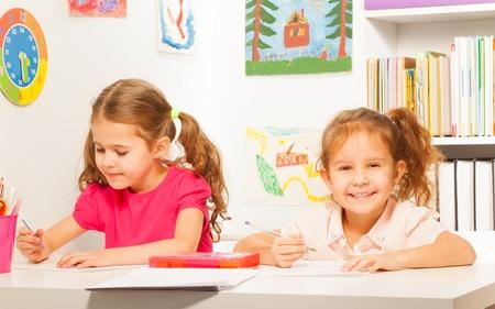 Dwie sprytne uczennice pisania piórem na zeszyt w klasie