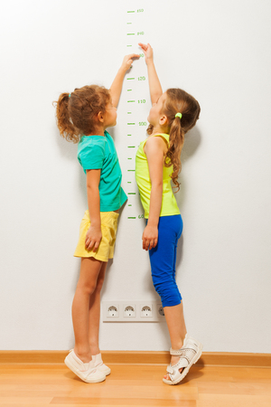 Two little girls standing by the wall and stretching hands on scale trying to reach high mark in full height portrait Archivio Fotografico