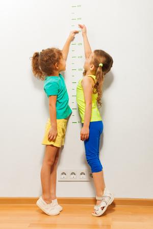 Zwei kleine Mädchen an der Wand stehen und Stretching Hände auf der Skala versuchen, hohe Marke in voller Höhe Porträt zu erreichen