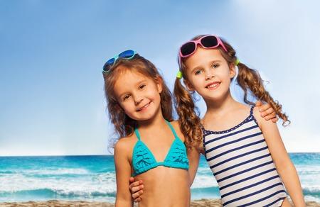 traje de baño: Dos amigos sonriendo poco en traje de baño y gafas de sol en la orilla del mar