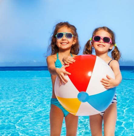 Dos chicas sonriente linda en traje de baño y gafas de sol que sostienen la bola inflable grande en sus manos en contra de cielo azul y el mar