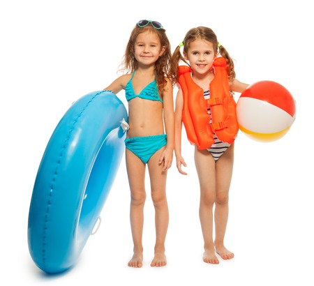 Two funny girls in swimwear with big blue rubber ring and colored wind-ball