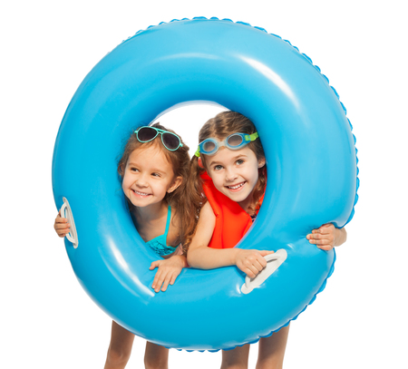 child swimsuit: Two smiling swimmers looking out big blue rubber ring holding it in their hands