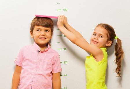 小さな 5 歳の女の子が壁にスケールで少年の高さを測定します。