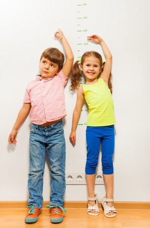 Two kids boy and little girl stand by the wall and show their height with hand above head