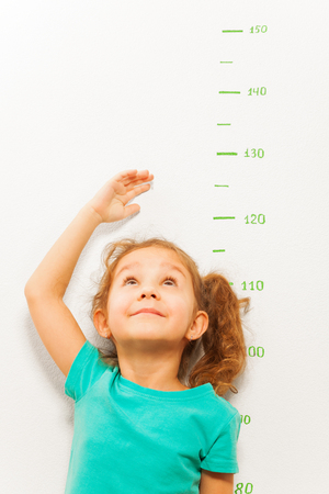 Portrait of little five years old girl stand by scale and measuring height with hand looking up and smile