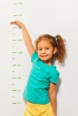 Kleines Mädchen, ihre Höhe mit der Hand auf die Wand gezeichnet auf einer Skala zeigen und Lächeln auf Gesicht Standard-Bild