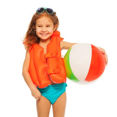 natacion niños: Muchacha sonriente feliz en gafas de sol y el chaleco salvavidas de color naranja con pelota de goma de color