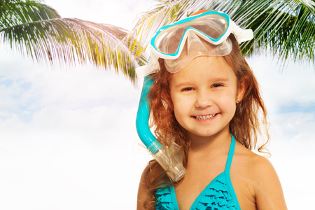 child laughing: Little smiling girl wearing blue swimwear with diving equipment against of green palm leafs