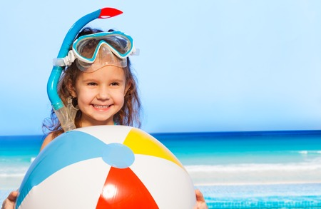 kid's day: Little smiling girl holding big multi-colored inflatable ball against of blue sky and tides