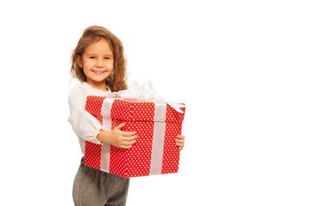 christmas present box: Nice little girl stand with Christmas present in big red box isolated on white