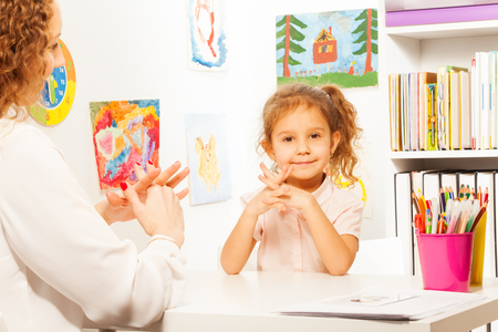 therapist: Teacher showing finger exercises to pupil at the table in bright classroom Stock Photo