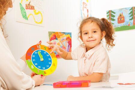 Muchacha que estudia horas y minutos en el reloj coloreado de cartón con un profesor Foto de archivo - 51261256