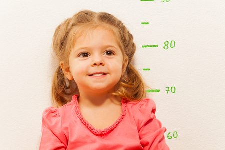 Smiling little girl is measuring her height against the painted green height chart