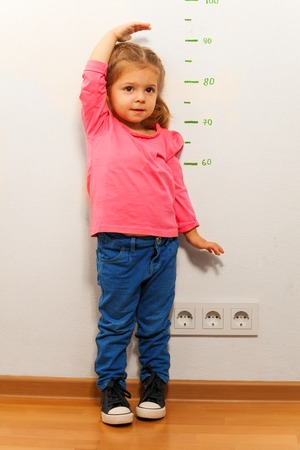 The girl measuring her height with her hand standing on the floor