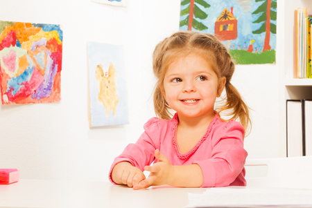 wall paintings: Little smiling girl with bunches sitting at the desk and viewing beautiful paintings at the wall Stock Photo
