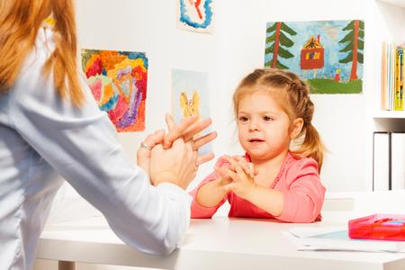 Jeden mały przedszkolak, grając w gry na palec z jej nauczycielem przy stole