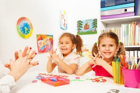 niños felices: Dos colegialas haciendo ejercicios de dedo como su maestro en el escritorio con los lápices y figuras matemáticas