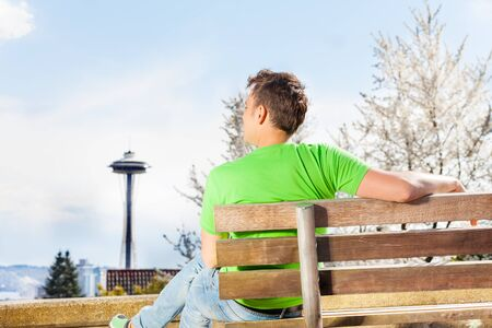 space needle: Handsome young man sitting on the bench and looking at Seattle space needle downtown tower