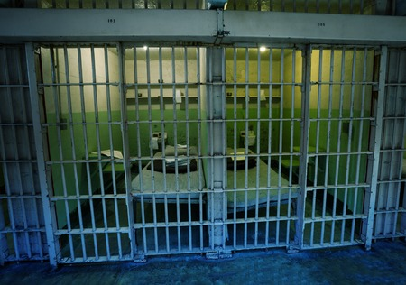 Typical old American prison cells with beds and other attributes behind the bars