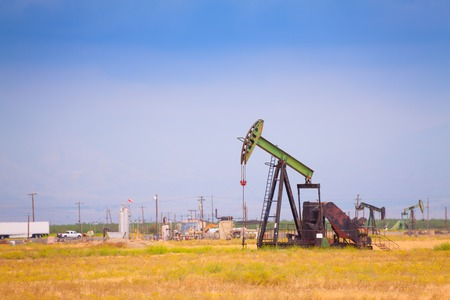 dug well: There are three steel oil-derricks at the bent manufacturing oil from the underground resources Stock Photo