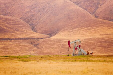 chink: One grey and red steel oil-derrick is pumping oil at the foot of the mountain