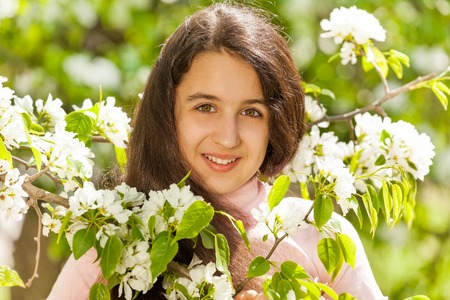 beautiful teen girl: Middle East teenager girl with white flowers on pear tree during sunny summer day in green park Stock Photo