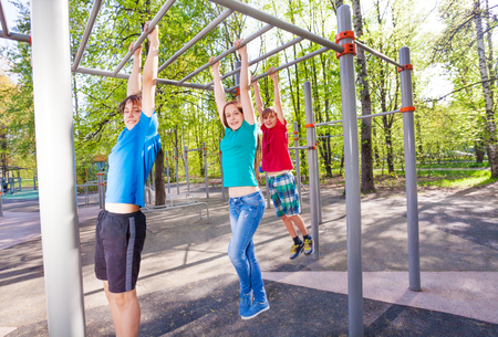 strong chin: Hanging teenagers on the brachiating bar at the sports ground during summer day with trees on background Stock Photo