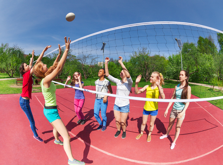 Fisheye view of teenagers playing volleyball on the game court outside during summer sunny day