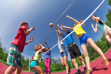 Jugendliche spielen Volleyball auf dem Spielplatz zusammen draußen im Sommer sonnigen Tag Standard-Bild