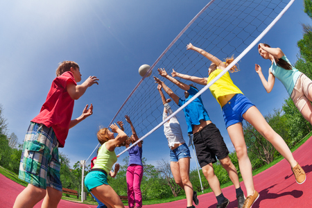 Teenagers playing volleyball on the game court together outside during summer sunny day Stock Photo