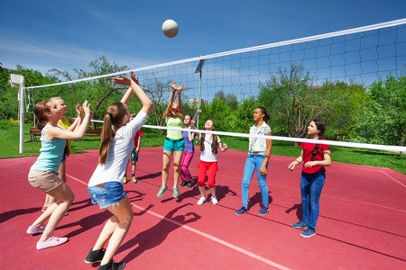 Teenage girls and boy play together volleyball outside on the playground during summer sunny day Archivio Fotografico