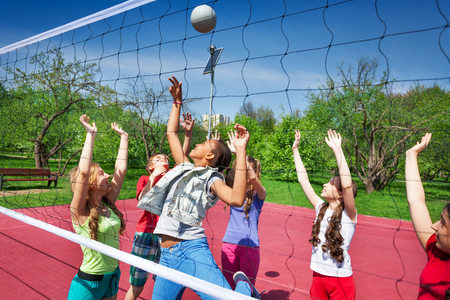 View through volleyball net of playing teens trying to catch the ball on the playground during summer sunny day
