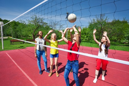 child sport: Teens playing during volleyball game on the playground during summer sunny day