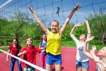 外の日当たりの良い夏の日の間に裁判所でバレーボールのネットに近い遊んで幸せなティーンエイ ジャー