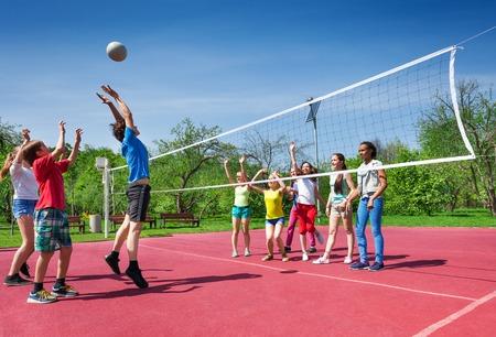 enfant qui joue: Sautant garçon pendant le jeu de volley-ball sur le terrain en journée d'été ensoleillée à l'extérieur