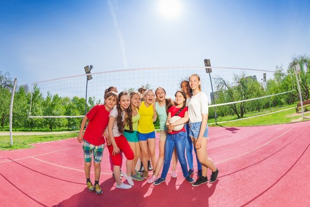 children clothing: Group of happy teen kids team posing together on the volleyball playground on sunny summer day