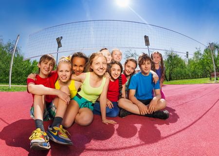 Gelukkige vrienden zitten op de volleybal spel rechter bedrijf bal in de zomer zonnige dag Stockfoto