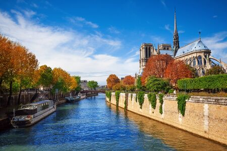 View of Notre Dame cathedral in Paris and  Seine river with boats embarked Imagens