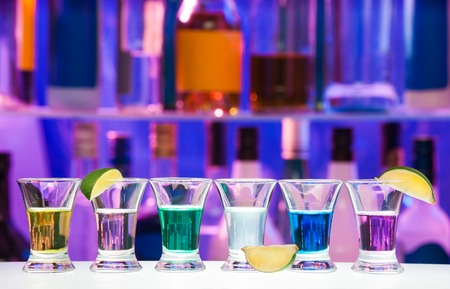 shooter drink: Row of shooter drinks on the bar table with many alcohol bottles on background