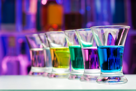 shooter drink: Color shoots perspective row in the dark bar bottles background Stock Photo