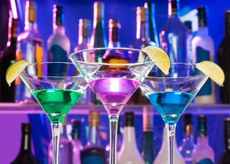 back in an hour: Shining cocktail glasses in the bar with limes with color lit bottles on back during happy hour Stock Photo