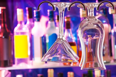 winy: Bar with bottles in the shelf and close-up on the glasses with dark night lights