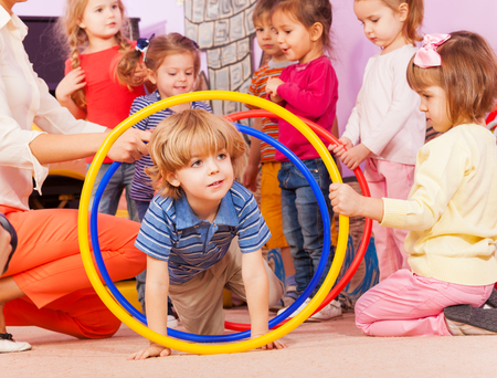 Cute boy play with boys and girls active game going though hoops in kindergarten