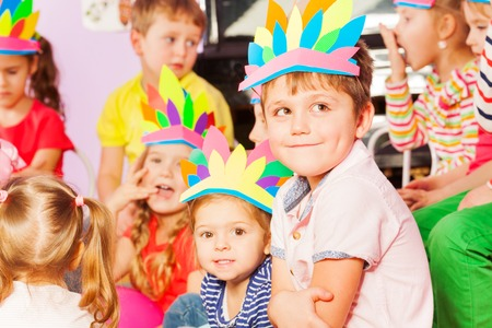 developmental: Close portrait of nice Caucasian boy sit in group of kids in developmental kindergarten class wearing handmade Indian headwear