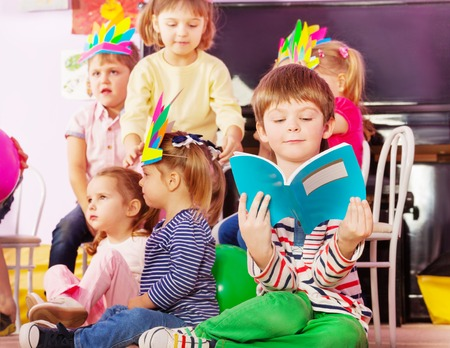 kindergarten education: Nice little boy learn to read from book sitting in developmental class with boys and girls on the back