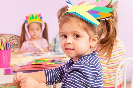 Little girl in crafting class wearing cardboard headwear working with paper and cardboard