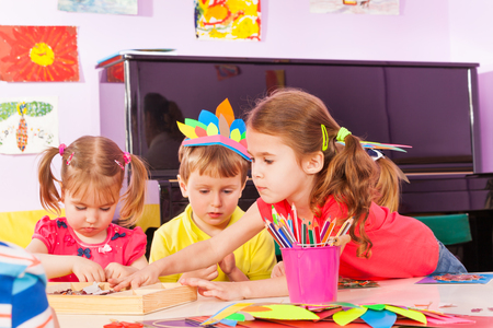 gluing: Little girl stretching for paper gluing in kindergarten class with other boys and girls