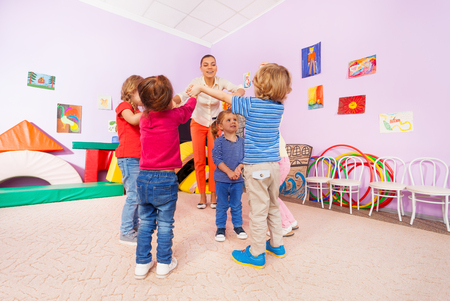 lifting hands: Group of kids boys and girls with teacher play roundelay around little girl lifting hands and coming close to each other Stock Photo