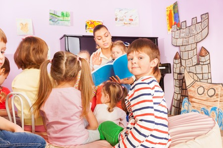 telling: Group of kids sit around teacher and listening to the story she reading with one boy turn back to camera
